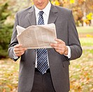 Businessman reading a newspaper in a park