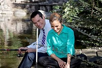 Business couple fishing in a river