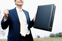 Businessman holding a briefcase and smiling in a field