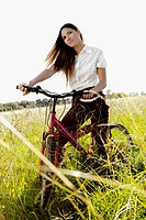 Teenage girl cycling in a field