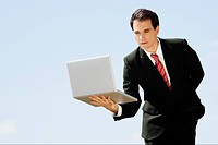 Businessman holding a laptop on his palm