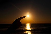 Person´s hand pretending to touch the setting sun, Miami Beach, Florida, USA