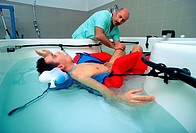 Physiotherapy for coma patient. Physiotherapist and patient during a session of physiotherapy in water. This stimulus maintains the body´s muscles and...