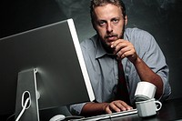 Work stress. Man smoking to help with stress while working at a computer.