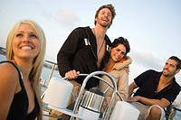 A group of friends sitting in the cockpit of a sailing yacht during an evening sail on San Diego Harbor, California.