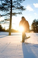 A young woman snowshoes through freshly fallen snow at sunset in Flagstaff, Arizona.