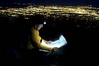 Woman reading map by headlamp.