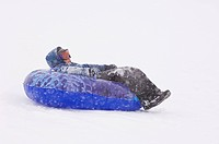 A boy sledding during snowstorm.