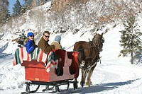 Three people riding sleigh.