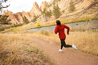 A woman trail running near a river.