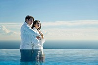 Couple embracing at edge of infinity pool, both wearing bathrobes