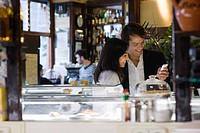 Couple looking at cell phone together in cafe