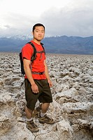 A young man with a backpack standing in the Devil´s Golf Course section of Death Valley National Park.