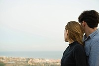 Couple embracing, looking at view