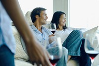 Couple enjoying red wine on sofa