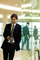 Businessman text messaging in lobby
