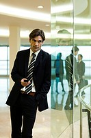 Businessman leaning against glass wall, using cell phone