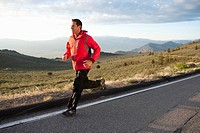 An athletic man running on a mountain road in South Lake Tahoe, California.