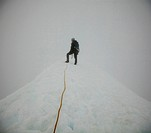 A climber stands on the summit of a peak on a white_out day as clouds surround him.