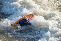 A male whitewater kayaker playboats on the Missoula play wave in the Clark Fork River, Missoula, Montana.