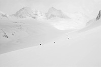 A group of backcountry skiers tour up a valley, dwarfed by the massive peaks of the Canadian Rockies shrouded in clouds.