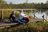 Young Couple Sitting on Wooden Boardwalk by Water in Meenikunno Landscape Reserve, Estonia