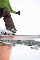 Blur of a snowboarder getting air off a ski park jump.