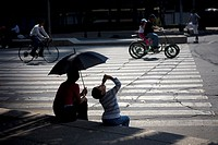 A boy drinks yogurt next to his mother holding an umbrella to shade them from the sun as they watch cyclists ride along Paseo de la Reforma Avenue in ...