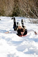 A man and woman enjoy a day of sledding activities in the mountains.