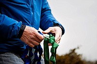 A man´s hands work with climbing gear at Palisades State Park, South Dakota.