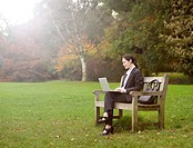 Business woman using laptop in park.