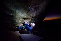 A young man attempts a boulder problem at the Lizzard´s Mouth during an amazing sunset.