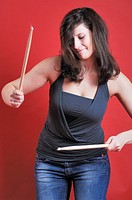 A young woman playing with drumsticks