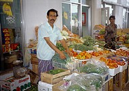 Fujairah UAE Fruit And Vegetable Souk Man Standing By His Stall Vegetables Covered In Plastic