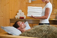 Italy, South Tyrol, Man having hay bath in hotel urthaler