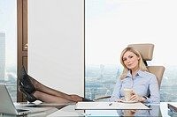 Germany, Frankfurt, Business woman sitting in office with coffee mug