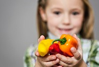 Girl holding bell peppers
