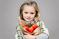 Girl holding fresh tomatoes, portrait