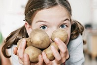 Germany, Cologne, Girl holding potatoes, portrait