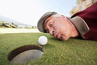 Italy, Kastelruth, Mature man blowing golf ball into hole