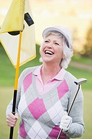 Italy, Kastelruth, Mature woman with golf club and golf flag on golf course, smiling