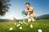 Italy, Kastelruth, Mid adult woman pouring basket of golf balls on golf course
