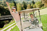 Italy, Kastelruth, Golfers in golf cart on golf course, smiling
