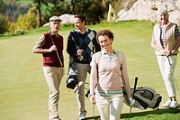 Italy, Kastelruth, Mid adult woman smiling with golfers in background on golf course