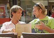 Germany, Nuremberg, Friends sitting at sidewalk cafe, smiling