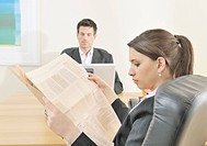 Businessman working on laptop and woman reading newspaper in office