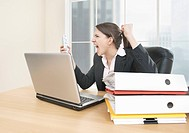 Businesswoman shouting angerily on mobile in office