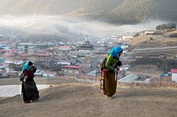 Tibetan pilgrims walking the Kora around temples, Stupas and monasteries in Langmusi, Gansu, China