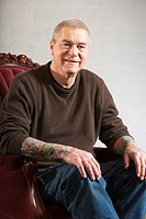 Portrait of a clean-cut, tattooed, mature man in the studio - smiling expression