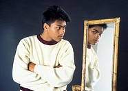 Portrait of an Asian teenage boy looking at himself in the mirror